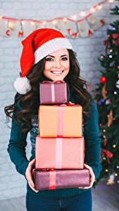 Bilder Neujahr Brünette Lächeln Mütze Geschenke junge frau