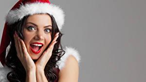 Fotos Neujahr Grauer Hintergrund Braune Haare Erstaunen Gesicht Hand Mädchens