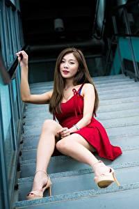 Fotos Asiatisches Stiege Braune Haare Kleid Sitzend Bein High Heels Unscharfer Hintergrund