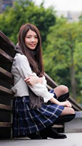 Hintergrundbilder Asiaten Unscharfer Hintergrund Sitzend Rock Braunhaarige Starren Lächeln Mädchens