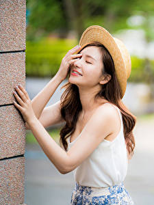 Fotos Asiaten Unscharfer Hintergrund Posiert Hand Unterhemd Der Hut Braune Haare junge frau