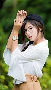Bilder Asiatisches Armbanduhr Unscharfer Hintergrund Barett Brille Blick Hand Pose Mädchens