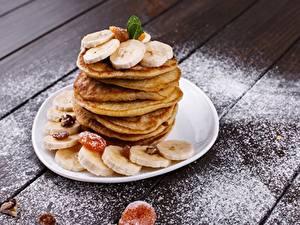 Bilder Eierkuchen Bananen Puderzucker Teller Bretter Lebensmittel
