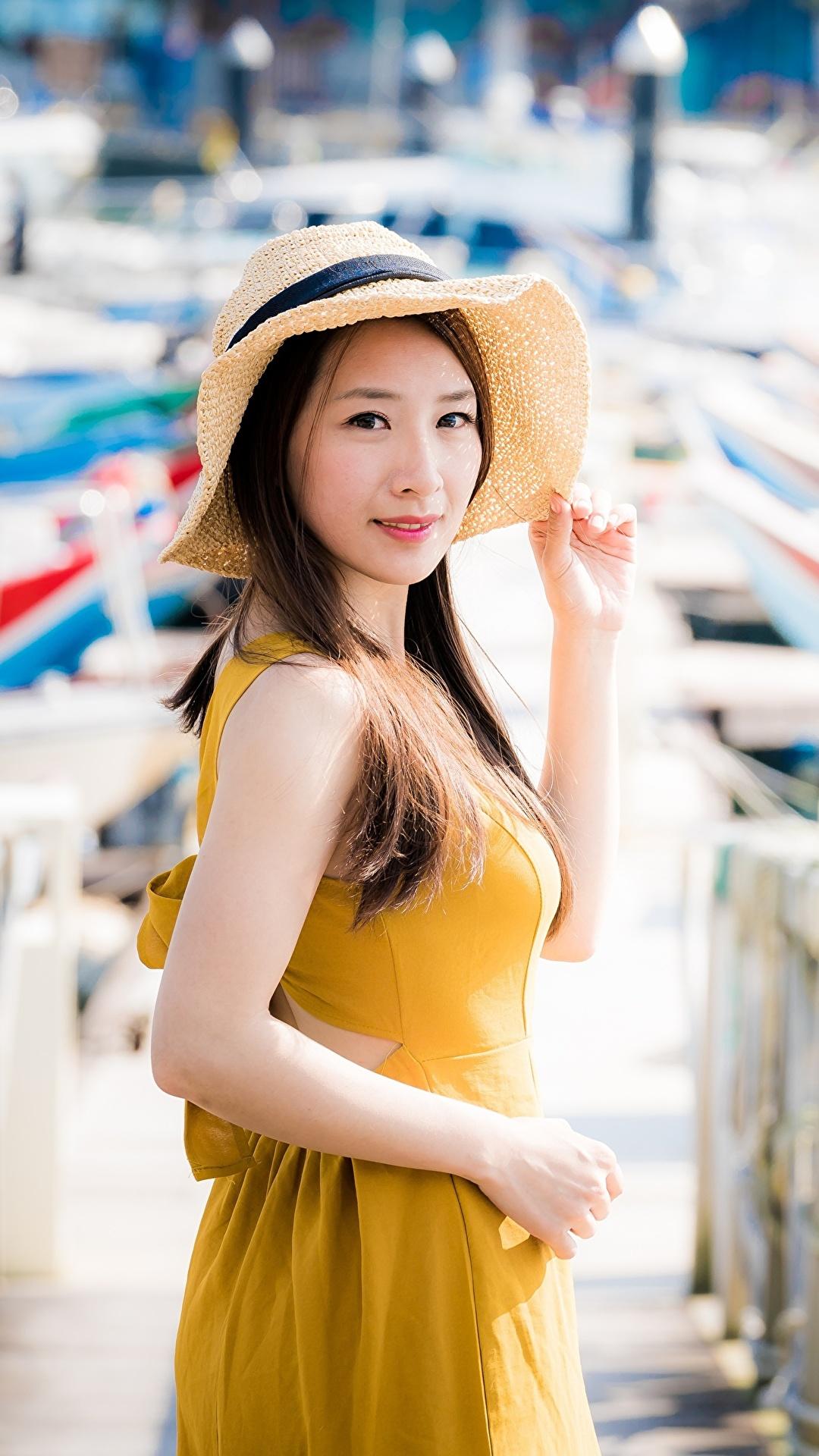 Foto Braunhaarige unscharfer Hintergrund Der Hut Mädchens Zaun Asiatische Hand Blick 1080x1920 für Handy Braune Haare Bokeh junge frau junge Frauen Asiaten asiatisches Starren