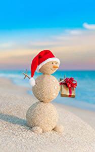 Bilder Neujahr Küste Schneemänner Mütze Geschenke Sand