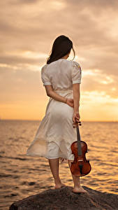 Fotos Meer Morgendämmerung und Sonnenuntergang Stein Violine Kleid Yaroslav Kotov junge frau Natur
