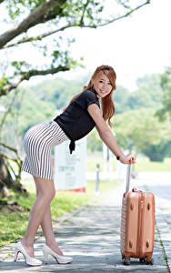 Fotos Asiaten Bokeh Braunhaarige Posiert Koffer Hand Rock Bein Stöckelschuh
