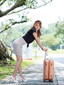 Fotos Asiaten Bokeh Braunhaarige Posiert Koffer Hand Rock Bein Stöckelschuh junge frau