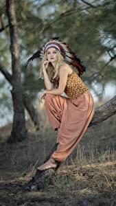 Bilder Federn Warbonnet Blondine Bokeh Posiert Sitzt Bäume Indianer Vicky Mädchens