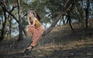 Bilder Federn Warbonnet Blondine Bokeh Posiert Sitzt Bäume Indianer Vicky