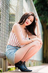 Hintergrundbilder Asiatisches Unscharfer Hintergrund Posiert Sitzend Rock Unterhemd Braunhaarige Blick Zaun junge Frauen