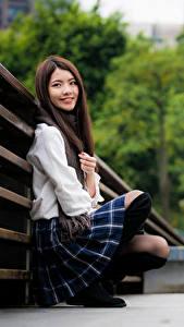 Fotos Asiatische Sitzt Lächeln Blick Bokeh Mädchens