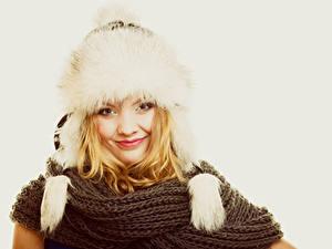 Fotos Grauer Hintergrund Blondine Lächeln Mütze Schal Mädchens