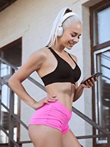 Fotos Fitness Blondine Lächeln Pose Kopfhörer Smartphone Shorts Unterhemd junge frau Sport