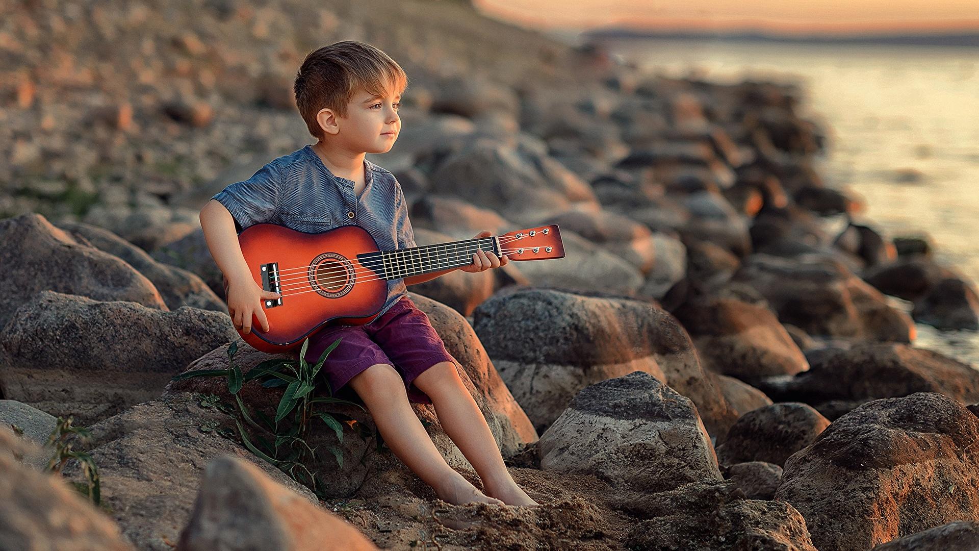 Fotos von jungen Gitarre Victoria Dubrovskaya Kinder sitzen Steine 1920x1080 Junge sitzt Sitzend