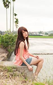 Fotos Asiaten Braune Haare Sitzen Unscharfer Hintergrund