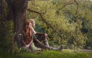 Pictures Elf Man The Hobbit Sit Grass Trunk tree Costume play Guy Legolas Tauriel LuckyStrikeCosplay young woman