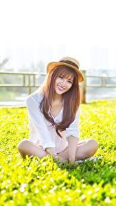 Bilder Asiatische Sitzend Lächeln Der Hut Braunhaarige junge Frauen