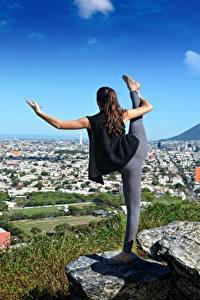 Bilder Stein Joga Dehnübung Braunhaarige Sport Mädchens