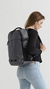 Bilder Grauer Hintergrund Braune Haare Rucksack Jeans Sweatshirt Mädchens