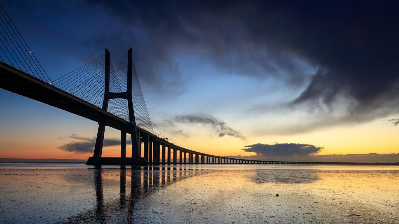 Tapety miasto Portugalia Vasco da Gama bridge Mosty Wieczór Lizbona 1366x768 Miasta most