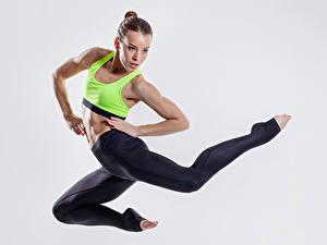Fotos Fitness Grauer Hintergrund Braunhaarige Sprung Hand Bein Mädchens Sport