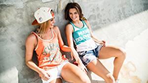 Fotos Lachen Lächeln Schöne Bein Unterhemd Shorts Zwei Sitzend Baseballcap junge Frauen