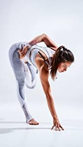Desktop hintergrundbilder Fitness Hand Bein Dehnübung Braunhaarige Posiert junge frau