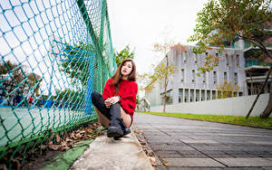 Bilder Asiatisches Sitzt Stiefel Bein Sweatshirt Zaun Blick junge frau