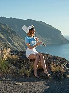 Desktop hintergrundbilder Steine Küste Gras Braunhaarige Der Hut Rock Sitzen Bein Mädchens