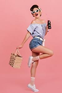 Bilder Handtasche Posiert Braunhaarige Brille Bein Shorts Bluse Flaschen Rosa Hintergrund junge frau