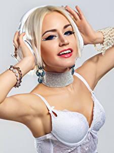 Fotos Schmuck Blondine Lächeln Kopfhörer Hand Büstenhalter Grauer Hintergrund junge Frauen