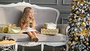 Fotos Neujahr Kleine Mädchen Sofa Sitzend Geschenke Weihnachtsbaum Kugeln Kinder