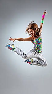 Pictures Gray background Brown haired Jump Smile Hands Joy Girls