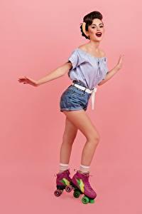 Hintergrundbilder Lächeln Braunhaarige Bein Rollschuh Shorts Bluse Rosa Hintergrund Mädchens