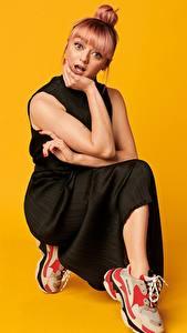 Bilder Maisie Williams Farbigen hintergrund Posiert Kleid Sportschuhe Hand Frisuren Blick Komische Prominente Mädchens
