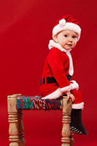 Bilder Neujahr Junge Weihnachtsmann Mütze Sitzen Starren Roter Hintergrund Kinder