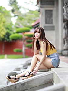 Fotos Asiaten Sitzt Bein Shorts Unterhemd Starren junge frau