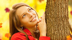 Images Brown haired Smile Staring Hands Trunk tree Girls