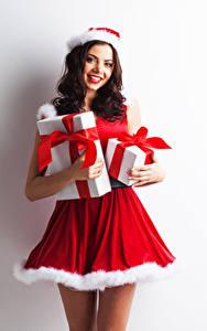 Fotos Neujahr Weißer hintergrund Uniform Braune Haare Lächeln Geschenke Starren Mädchens