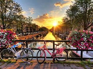 Desktop hintergrundbilder Brücken Sonnenaufgänge und Sonnenuntergänge Niederlande Amsterdam Sonne Fahrräder Städte
