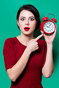 Pictures Clock Fingers Alarm clock Colored background Brunette girl Staring Red lips young woman