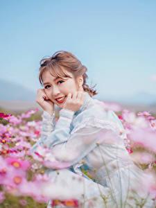 Fotos Grünland Asiaten Unscharfer Hintergrund Sitzt Kleid Hand Lächeln Niedlich Braune Haare Starren Natur Blumen