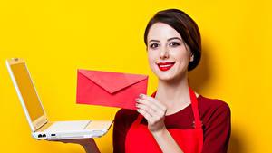 Fotos Farbigen hintergrund Braunhaarige Lächeln Rote Lippen Notebook Hand Brief Mädchens