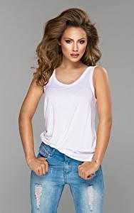 Fotos Grauer Hintergrund Braune Haare Starren Unterhemd Jeans Hand Mädchens