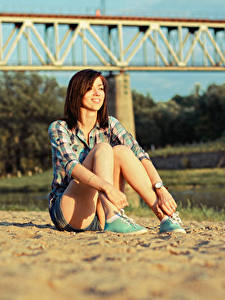 Hintergrundbilder Sand Unscharfer Hintergrund Braunhaarige Lächeln Sitzend Hand Bein Mädchens