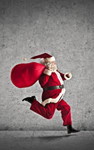 Fotos Neujahr Grauer Hintergrund Weihnachtsmann Laufsport Geschenke