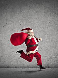 Fotos Neujahr Grauer Hintergrund Weihnachtsmann Lauf Laufen