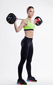 Fotos Fitness Grauer Hintergrund Braune Haare Trainieren Hantelstange Uniform Mädchens Sport