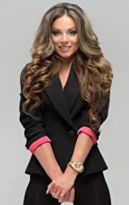 Bilder Armbanduhr Grauer Hintergrund Hand Model Haar Lächeln Blick Lilia Kapitonova junge Frauen